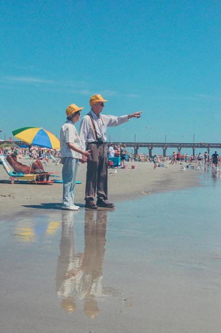 Deux personnes âgées sont à la plage, habillés et portant des chapeaux jaunes. Ils se donnent la main. L'homme pointe quelque chose vers l'horizon.